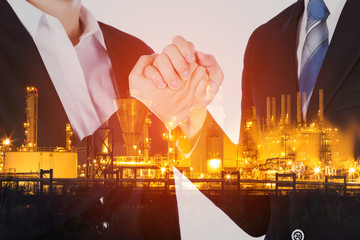 double exposure of arm wrestling between businessman and businesswoman with oil refinery plant background
