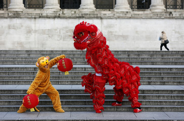 Performers in a lion and a monkey costume pose during a photo call to welcome in the Chinese New Year of the Monkey in Trafalgar Square