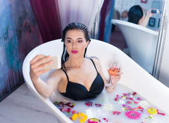 Sexy brunette woman taking selfie with glass of champagne having a hot milk bath with flower Petals. she is wearing black sexual lingerie