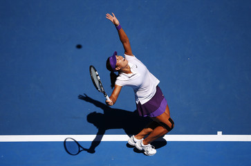 Li Na of China serves to Maria Sharapova of Russia during their women's singles semi-final match at the Australian Open tennis tournament in Melbourne