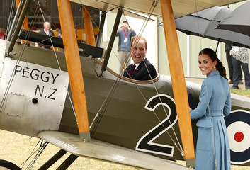 Britain's Prince William laughs as his wife, Catherine, the Duchess of Cambridge, stands next to a Sopwith Pup vintage plane he is sitting in near Blenheim