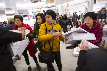 Women pass boxes of shoes in Macy's to kick off Black Friday sales in New York