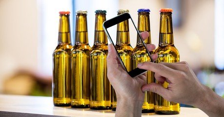 Hand taking picture of beer bottles through smart phone