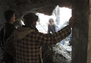 Residents remove debris after what activists said was shelling from forces loyal to Syria's President Bashar Al-Assad in Eastern Ghouta