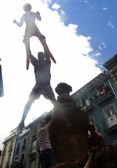 A man leaps from a fountain holding a blow-up doll following the midday Chupinazo rocket announcing the start of the San Fermin festival in Pamplona