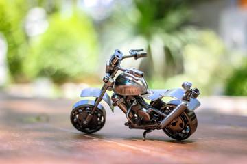 Steel chopper motorbike model with blur outdoor background.