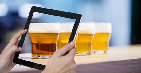 Hand taking picture of beer glasses with digital tablet in bar