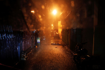 Heavy rain pours as the body of a man killed by unidentified gunmen riding motorcycles is left in a narrow alley in Manila