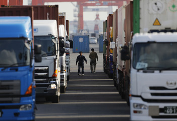 Workers walk between cargo containers loaded on trucks at a pier in Tokyo