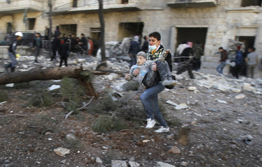 A man carries a wounded boy who survived what activists say was an air strike by forces loyal to Syrian President Assad in Aleppo's al-Ansari al-Sharqi neighbourhood