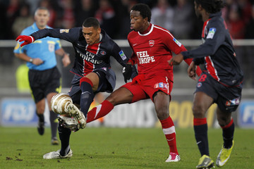 Paris St. Germain's Guillaume Hoarau challenges Valenciennes'Carlos Sanchez Moreno during their French League Cup soccer match in Valenciennes