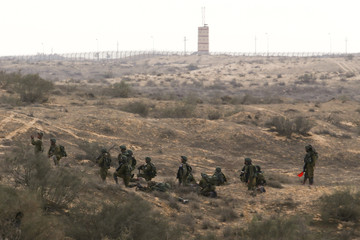 The Egyptian border fence is seen in the background as Israeli soldiers from the Desert Reconnaissance battalion take part in a drill near Kissufim in southern Israel