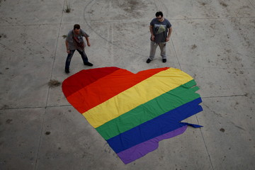 Fer Franco, 25, and his partner Rafa Varon, 23, stand next to a heart-shaped cloth with rainbow colors as they pose for a photo, to mark Gay Pride day, in downtown Malaga