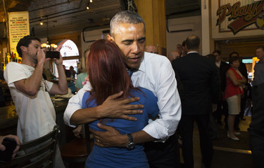 U.S. President Barack Obama hugs Kalynne May Arrick after she told Obama her brother was killed while serving in Afghanistan during a stop in a bar in Denver