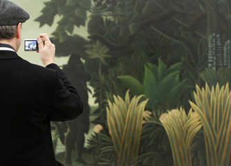 "A man takes pictures of the painting ""The Snake Charmer"" by French painter Rousseau at the Fondation Beyeler in Riehen"