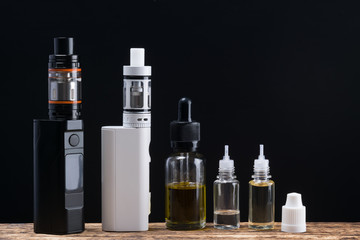 A set of electronic smoking appliances laid out on a table, on a black background