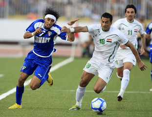 Kuwait's Fahed Al Eneysi fights for the ball with Iraq's Ali Rihayma during the semi-final of the Gulf Cup soccer tournament in Aden