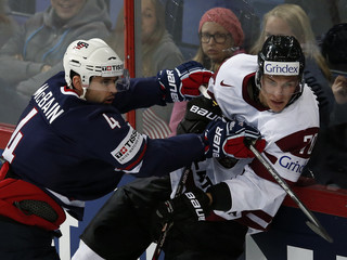Team USA's McBain checks Latvia's Indrasis against the glass during their 2013 IIHF Ice Hockey World Championship preliminary round match at the Hartwall Arena in Helsinki