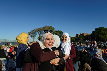 People greet each other before a group prayer session for the Muslim holiday Eid al-Adha in the Brooklyn borough of New York City