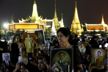 Mourners hold up pictures of Thailand's late King Bhumibol Adulyadej during a vigil to mark his birthday outside the Grand Palace in Bangkok