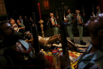 Spanish legionnaires stand at attention during a change of honor guard near the statue of the Christ of Mena inside a chapel during Holy Week in Malaga