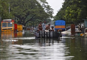 Flood-affected people use a piece of a plastic water tank as they make their way to the market to buy food items in a flooded locality in Chennai