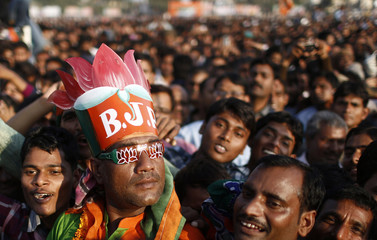 A supporter of India's main opposition BJP wears a hat and goggles supporting the party's lotus symbol during a rally being addressed by Hindu nationalist Narendra Modi in Agra