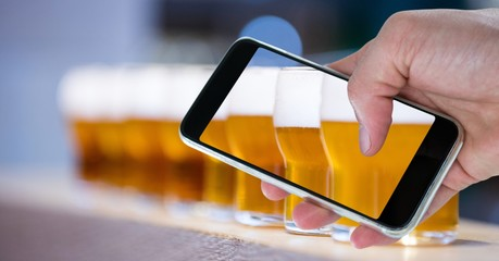 Hand taking picture of beer glasses through smart phone