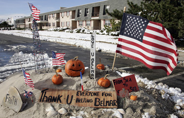 A pile of sand on Ocean Avenue bears a thank you messages and American Flags in Belmar