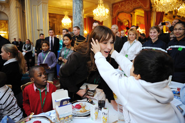 French First Lady Carla Bruni-Sarkozy receives a kiss from a child during the Christmas party at the Elysee Palace in Paris