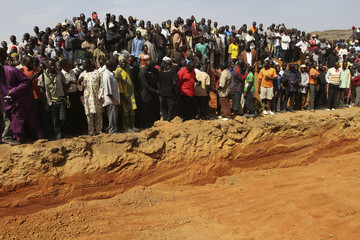 People stand by a grave before a mass burial of victims killed in religious attacks in the Dogo Nahawa village