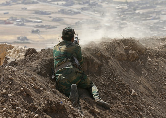 A Kurdish Peshmerga fighter fires at Baretle village, which is controlled by the Islamic State, in Khazir