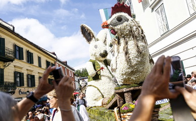 People take pictures of a giant chicken and a bunny, made out of daffodil flowers, during a parade at the Narzissenfest (Daffodil Festival) along Grundlsee lake in the village of Bad Aussee