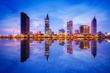 Cityscape in reflection of Ho Chi Minh city at beautiful twilight, viewed over Saigon river. Hochiminh city is the largest city in Vietnam with population around 10 million people