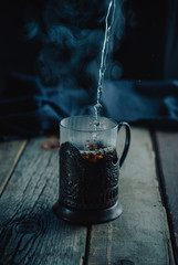 Very hot tea with steam, pouring into a glass in a cup holder on a wooden vintage rustic table. Black background. Dark and moody. Toned picture. Close up, selective focus