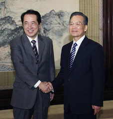 Japan's FM Kan shakes hands with Chinese Premier Wen before their meeting in Beijing