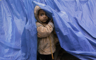 A child looks out from his shelter made up of tarpaulin at a pavement on a cold winter morning in Noida