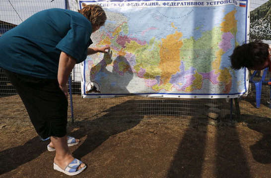 People look at a map of Russia at a temporary camp set up for Ukrainian refugees outside Donetsk
