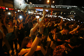 Protesters hold up their mobile phones with the flash light function switched on, as they block the main street to the financial Central district in Hong Kong