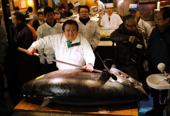 Kiyoshi Kimura poses for pictures with a bluefin tuna at his sushi restaurant outside Tsukiji fish market in Tokyo