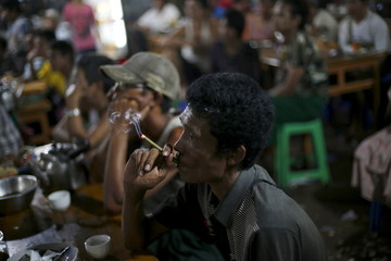 A man smokes while watch movies in a market in Yangon