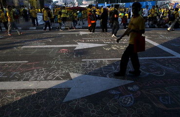 """Supporters of pro-democracy group """"Bersih"""" gather along a street on which messages and drawings have been chalked, outside Dataran Merdeka in Malaysia's capital city of Kuala Lumpur"""