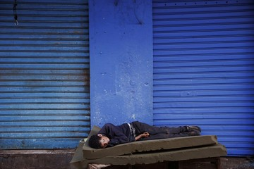 A man sleeps in front of a closed shop in Rabat's Medina