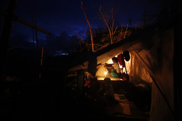 Homeless survivors live in a makeshift house in a community devastated by Typhoon Haiyan in Tacloban City central Philippines