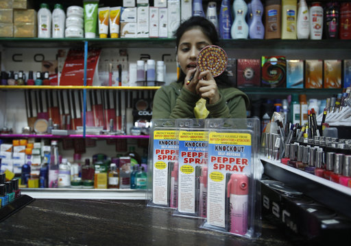 A salesgirl applies lipstick inside a shop with bottles of pepper spray displayed for sale in New Delhi
