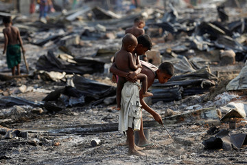 Boys search for useful items among the ashes of burnt houses after fire destroyed shelters at a camp for internally displaced Rohingya Muslims in the western Rakhine State near Sittwe
