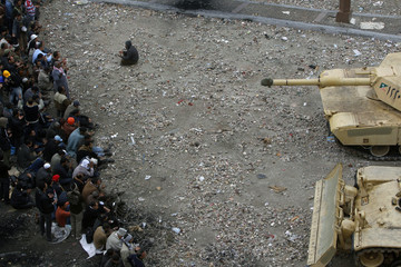 An anti-government protester prays as his comrades stand behind barbed wire in front of army tanks on the front line near Tahrir Square in Cairo