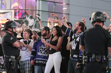 Los Angeles Police Officers watch as fans celebrate outside Staples Center after the Los Angeles Kings won the Stanley Cup in Los Angeles