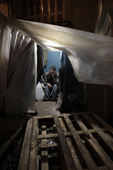 An immigrant speaks on his mobile inside a tent in a building's yard in Athens
