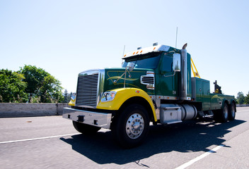 Big rig equipped towing semi truck on road